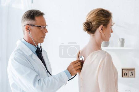 handsome doctor in glasses examining woman in clinic
