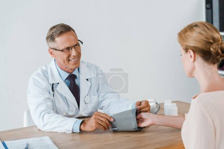 Photo for Selective focus of happy doctor measuring blood pressure of woman - Royalty Free Image