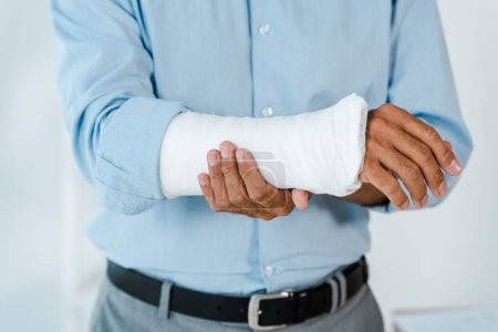 Photo for Cropped view of injured man touching broken arm wrapped in gypsum bandage - Royalty Free Image