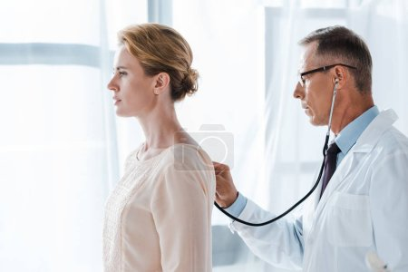 Photo for Side view of doctor in glasses using stethoscope while examining attractive patient in clinic - Royalty Free Image