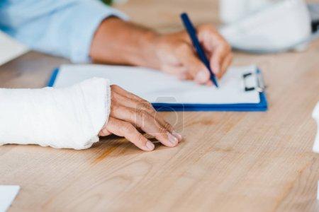 Photo pour Vue recadrée de l'homme blessé avec le bandage de gypse sur l'écriture cassée de bras sur le clipboard - image libre de droit