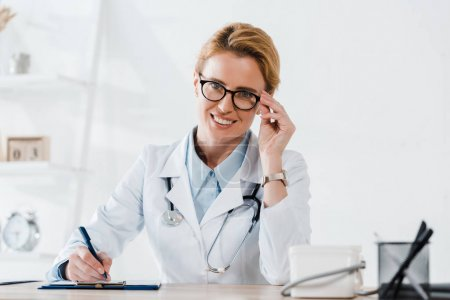 Photo for Happy doctor touching glasses and writing diagnosis in clinic - Royalty Free Image