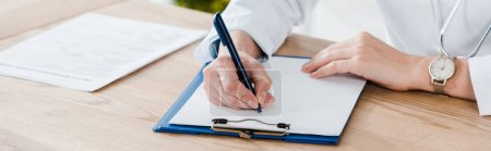 Photo for Panoramic shot of doctor writing diagnosis on wooden table - Royalty Free Image