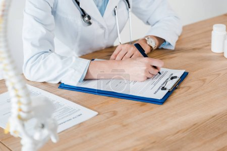 Photo for Cropped view of doctor writing diagnosis on wooden table - Royalty Free Image