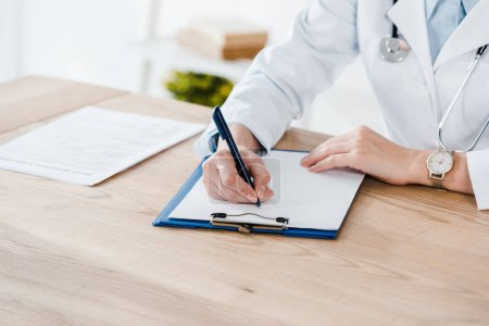 Photo for Cropped view of doctor in white coat writing diagnosis on wooden table - Royalty Free Image