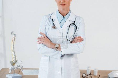 Photo pour Vue recadrée du médecin debout avec les bras croisés à l'hôpital - image libre de droit