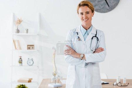 Photo pour Médecin attrayant et positif debout avec les bras croisés dans la clinique - image libre de droit