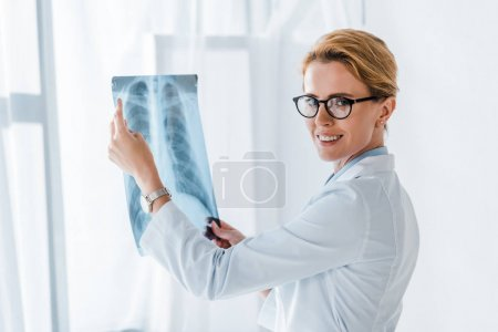 Photo for Happy and attractive doctor in glasses holding x-ray in clinic - Royalty Free Image