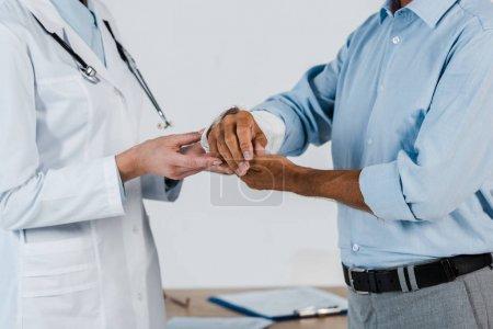 Photo pour Vue recadrée du médecin touchant le bras cassé sur le patient à la clinique - image libre de droit