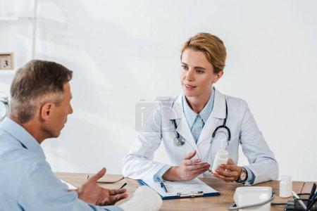 Photo pour Foyer sélectif du docteur attrayant regardant l'homme avec le bras cassé tout en retenant la bouteille - image libre de droit