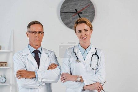 Photo pour Beau docteur restant avec les bras croisés près du collègue gai dans la clinique - image libre de droit
