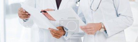 Photo pour Photo panoramique de médecins tenant des papiers dans la clinique - image libre de droit