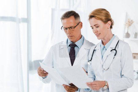 Photo for Handsome doctor in glasses and attractive coworker holding papers in clinic - Royalty Free Image