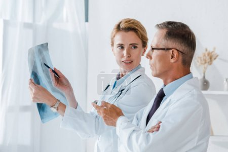 Photo for Attractive doctor holding pen and x-ray near coworker gesturing in clinic - Royalty Free Image