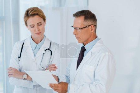 Photo pour Homme en lunettes et manteau blanc regardant du papier vierge près d'un collègue avec les bras croisés - image libre de droit