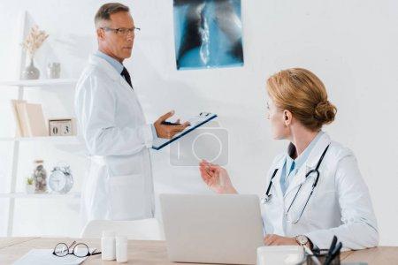 Photo pour Beau médecin debout près de la radiographie et en regardant collègue - image libre de droit
