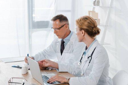 Photo pour Beau médecin dans des lunettes près de collègues attrayants gesticulant et en utilisant l'ordinateur portable - image libre de droit