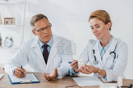 Photo for Handsome doctor in glasses gesturing while looking at bottle near cheerful colleague - Royalty Free Image