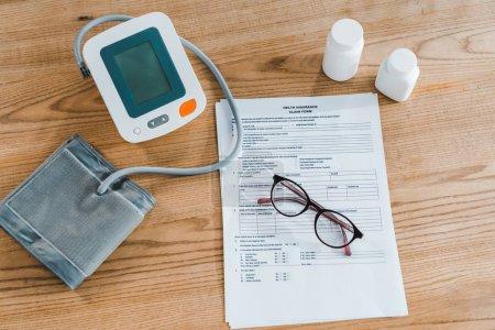 Photo pour Vue de dessus du tensiomètre près du document et des lunettes - image libre de droit