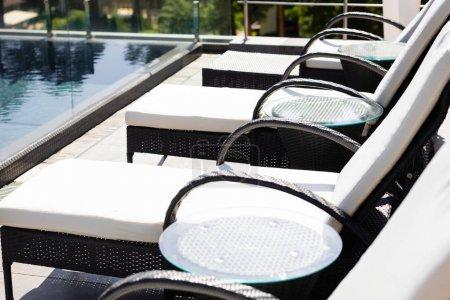 Photo pour Lits de soleil près de la piscine sur la station pendant la journée - image libre de droit