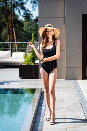 Photo pour Belle femme dans le maillot de bain et le chapeau de paille posant près de la piscine - image libre de droit