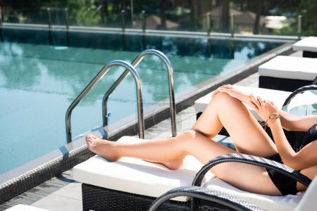 Photo for Partial view of woman in swimming suit lying on sun bed near swimming pool - Royalty Free Image