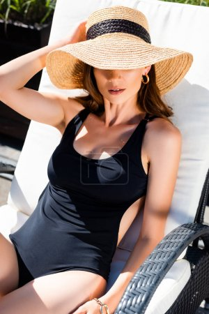 Photo for Sexy girl in swimming suit and straw hat lying on sun bed on resort - Royalty Free Image