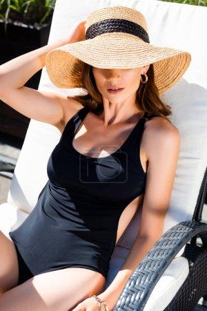 Photo pour Fille sexy dans le maillot de natation et le chapeau de paille se trouvant sur le lit de soleil sur la ressource - image libre de droit