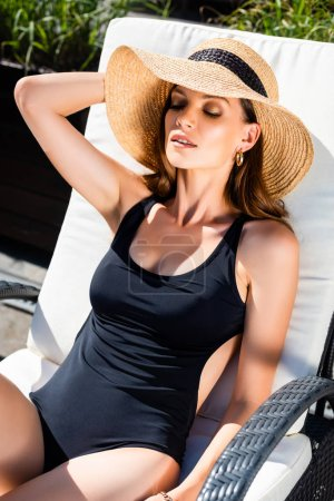 Photo for Beautiful girl in swimming suit and straw hat resting on sun bed on resort - Royalty Free Image