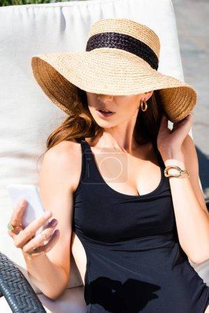 Foto de Chica en traje de baño y sombrero de paja acostado en la cama solar y el uso de teléfono inteligente en el complejo - Imagen libre de derechos