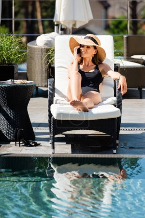 Photo pour Femme dans le procès-il de natation se trouvant sur le lit de soleil et parlant sur le smartphone près de la piscine - image libre de droit