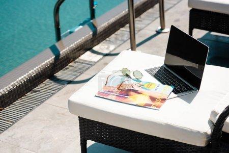 Foto de Portátil con pantalla en blanco, revista y gafas de sol en la cama solar cerca de la piscina - Imagen libre de derechos