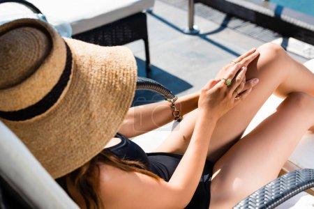 Photo pour Fille sexy en maillot de bain et chapeau de staw couché sur un transat en station balnéaire - image libre de droit
