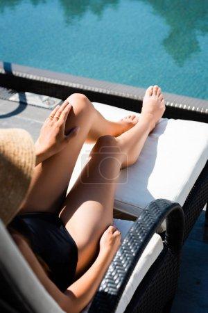 Photo pour Vue cultivée de femme dans le procès de natation se trouvant sur le lit de soleil près de la piscine - image libre de droit