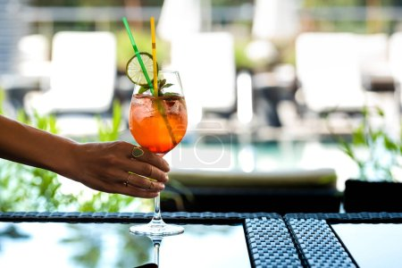 Photo for Cropped view of woman holding cocktail with mint and lemon on resort - Royalty Free Image