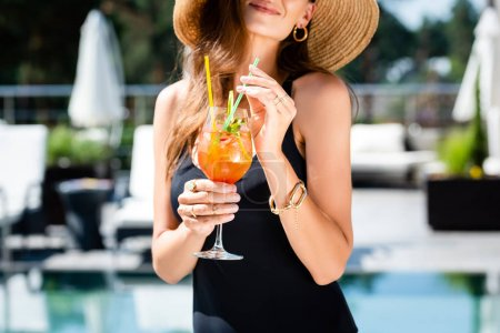 Photo for Cropped view of woman in swimming suit with Straw Hat and cocktail on resort - Royalty Free Image