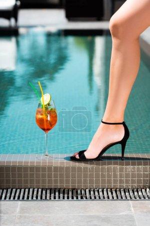 Photo pour Vue cultivée de femme dans la chaussure près du cocktail et de la piscine sur la ressource - image libre de droit