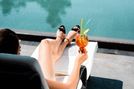 Photo pour Vue cultivée de femme près de la piscine avec le cocktail sur la ressource - image libre de droit
