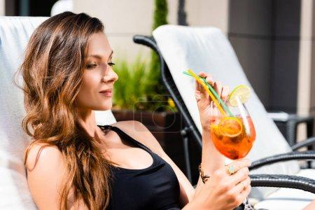 Photo pour Belle fille dans le costume de natation se trouvant avec le cocktail sur le lit de soleil - image libre de droit