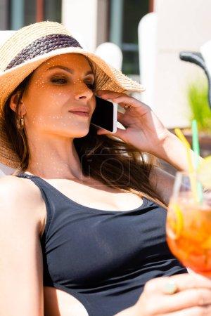 Photo pour Belle fille dans le maillot de bain avec le cocktail sur le lit de soleil parlant sur le smartphone - image libre de droit