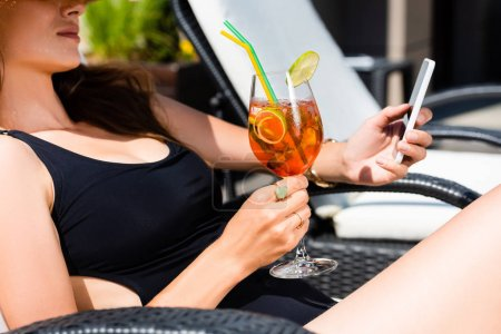Ausgeschnittene Ansicht eines Mädchens im Badeanzug mit Cocktail auf der Sonnenbank per Smartphone
