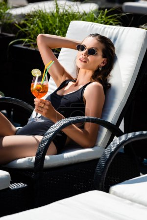 Photo for Beautiful girl in swimming suit lying with cocktail on sunbed - Royalty Free Image