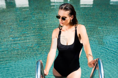 Foto de Hermosa mujer en gafas de sol posando en la piscina en el complejo - Imagen libre de derechos