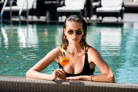 Photo pour Belle fille dans des lunettes de soleil avec le cocktail dans la piscine sur la ressource - image libre de droit