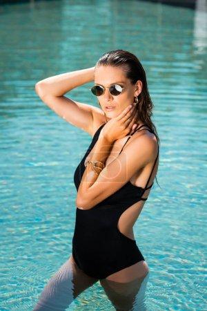 Foto de Beautiful woman in sunglasses posing in swimming pool - Imagen libre de derechos