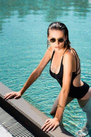 Photo pour Belle femme dans des lunettes de soleil posant dans la piscine - image libre de droit