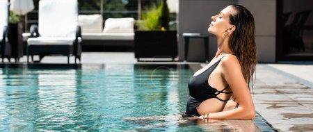 panoramic shot of beautiful woman in swimming suit posing in swimming pool