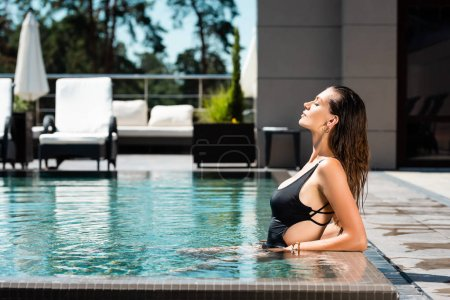 Photo for Side view of beautiful woman in swimming suit posing in swimming pool - Royalty Free Image
