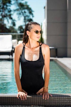 Photo pour Femme sexy attirante dans le maillot de natation et les lunettes de soleil posant près de la piscine sur la ressource - image libre de droit