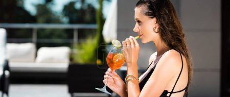 Photo for Panoramic shot of beautiful young woman in swimming suit drinking cocktail on resort - Royalty Free Image